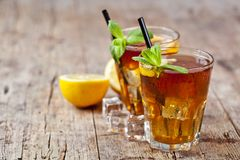Traditional Iced Tea With Lemon, Mint Leaves And Ice Cubes In Two Glasses On Rustic Wooden Table Background Royalty Free Stock Photography