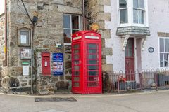Traditional iconic British red telephone box in a street in Cornwall, England stock image