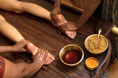 Traditional indian ayurvedic oil foot massage. Indian doctors doing traditional ayurvedic oil foot massage royalty free stock photography