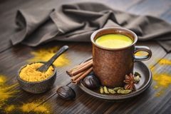 Traditional Indian drink turmeric milk. Is golden milk with cinnamon, cloves, pepper and turmeric on a wooden background with spices stock photo