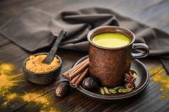 Traditional Indian drink turmeric milk. Is golden milk with cinnamon, cloves, pepper and turmeric on a wooden background with spices royalty free stock images