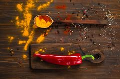 Traditional Indian flowers Holi, spices, a large wooden spoon and red pepper on a dark background. Background with spices. Spices. Top view. The concept of Royalty Free Stock Images