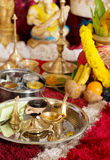 Traditional Indian Hindu religious ceremony. Traditional Indian Hindu religious praying items in ear piercing ceremony for children. Focus on the oil lamp. India Royalty Free Stock Photography