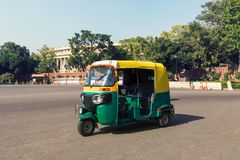 Traditional indian moto rickshaw taxi on one. Tuk tuk - traditional indian moto rickshaw taxi on one of the street of New Delhi. yellow green tricycle stands on stock image