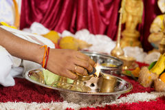 Traditional Indian religious praying ceremony. Traditional Indian Hindu religious praying items in ear piercing ceremony for children. Focus on the hand and oil Royalty Free Stock Photography