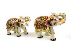 Figures of a pair of white elephants in marble with red and gold painting isolated on white background Traditional Indian souvenir royalty free stock photos