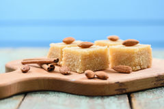 Traditional Indian sweetmeats, semolina halava with almonds on w. Ooden board copyspace side view Royalty Free Stock Photo