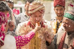 Traditional Indian Wedding. Shimla, India – April 19, 2017: Bride's family feed sweet to groom as his relatives, friends and family look on during a welcome Stock Photography