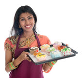 Traditional Indian woman baking cupcakes. Happy Traditional Indian woman in sari baking bread and cupcakes, wearing apron holding tray isolated on white Royalty Free Stock Image