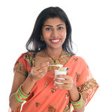 Traditional Indian woman eating yogurt. Happy Traditional Indian woman in sari eating yogurt, isolated on white background Stock Image