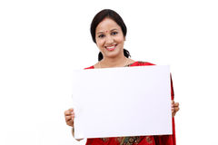 Traditional Indian woman holding a blank billboard. Cheerful traditional Indian woman holding a blank billboard stock photo