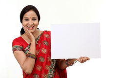 Traditional Indian woman holding a blank billboard Royalty Free Stock Image