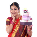 Traditional Indian woman holding gift boxes against white Royalty Free Stock Photos