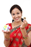 Traditional Indian woman holding a piggy bank Royalty Free Stock Photos