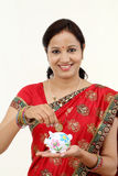 Traditional Indian woman holding a piggy bank Stock Photography