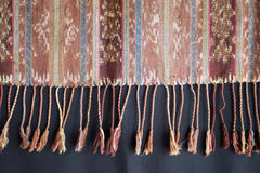 Traditional Indonesian and Asian pattern on fabric with tassels. Traditional Indonesian and Asian pattern on fabric with brushes closeup and details Royalty Free Stock Image