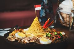 Traditional Indonesian Cuisine Nasi Tumpeng. For Independence Celebration with Flag. Tumpeng is a cone-shaped rice dish like mountain with meats royalty free stock photography