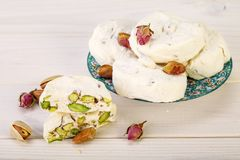 Traditional Iranian and Persian pieces of white nougat dessert sweet candies Gaz with Pistachio. Close up Traditional Iranian and Persian pieces of white nougat Stock Photo