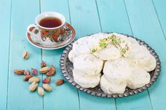 Traditional Iranian and Persian pieces of white nougat dessert sweet candies Gaz with Pistachio nuts. From Isfahan City and a cup of tea on blue turquoise wood Stock Image