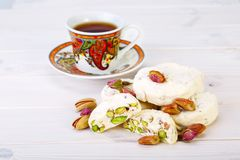 Traditional Iranian and Persian pieces of white nougat dessert sweet candies Gaz with Pistachio nuts. From Isfahan City and a cup of tea on white wooden Royalty Free Stock Images