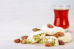 Traditional Iranian and Persian pieces of white nougat dessert sweet candies Gaz with Pistachio nuts. From Isfahan City and a cup of tea on white wooden Royalty Free Stock Photos