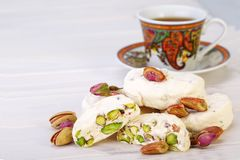 Traditional Iranian and Persian pieces of white nougat dessert sweet candies Gaz with Pistachio nuts. From Isfahan City and a cup of tea on white wooden Stock Images