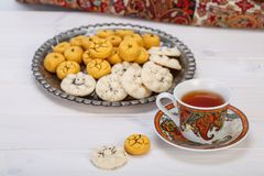 Traditional Iranian Sweets Round shaped Chickpea cookie pastries. And rice cookies in Persian Toreutic plate with a close up shot of paisley design cup and Stock Photos