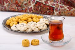 Traditional Iranian Sweets Round shaped Chickpea cookie pastries. And rice cookies in Persian Toreutic plate with a close up shot of glass cup and saucer tea on Stock Photos