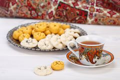 Traditional Iranian Sweets Round shaped Chickpea cookie pastries. And rice cookies in Persian Toreutic plate with a close up shot of paisley design cup and Royalty Free Stock Photos