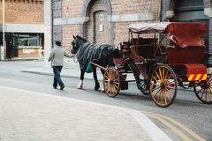 Traditional Irish Carriage. Cheerful Irish man walks his horse and carriage outside the guinness storehouse looking for business.  26 Oct 2016 Royalty Free Stock Photos