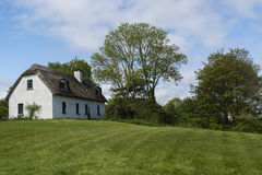 Traditional Irish cottage house next to trees Stock Photos