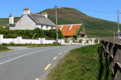 Traditional Irish farm house with barn, Dingle Peninsula, Ireland. A country road curves past a white farm house and a barn with a weathered orange metal roof Royalty Free Stock Image