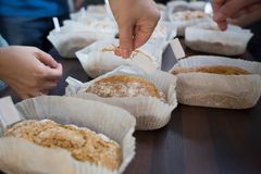 Traditional irish soda bread cooking class. Freshly cooked Irish soda bread loafs wrapped in cooking paper for breakfast. people`s hands Royalty Free Stock Photography