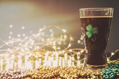 St Patricks Day Irish Stout Beer. Traditional Irish stout, a dark beer. On a pub bar rail table with lights and St Patrick`s Day party beads Stock Images