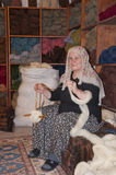 Traditional Islamic Woman Working on a Rug Stock Image