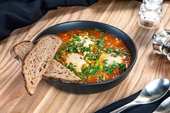 Traditional Israeli dish shakshuka, tomato scrambled eggs with vegetables. Close up on shakshuka in bowl with parsley and bread. stock images