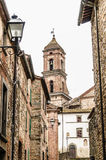 Traditional Italian Alley. Traditional italian village alley with stone wall, street lamps and a church steeple Royalty Free Stock Photography