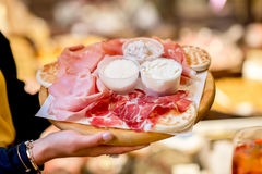Traditional italian aperitif. Female hands holding traditional italian aperitif with proscioutto, mortadella sausage and cheese on the wooden board with blurred stock photo