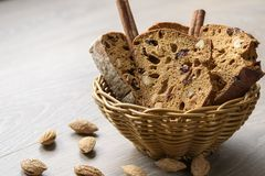 Traditional Italian biscotti Almond Cantuccini in a basket decorated with nuts on wooden table. Traditional Italian biscotti Almond Cantuchini in a basket Stock Photos