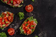 Traditional Italian Bruschetta with chopped tomatoes, mozzarella sauce, salad leaves and ham on a dark baton background. royalty free stock photography