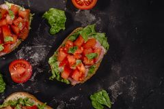 Traditional Italian Bruschetta with chopped tomatoes, mozzarella sauce, salad leaves and ham on a dark baton background. royalty free stock photo
