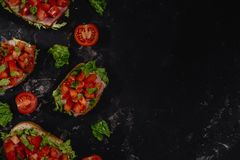 Traditional Italian Bruschetta with chopped tomatoes, mozzarella sauce, salad leaves and ham on a dark baton background. stock images