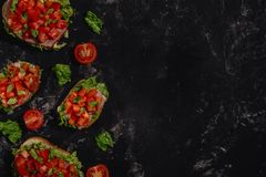 Traditional Italian Bruschetta with chopped tomatoes, mozzarella sauce, salad leaves and ham on a dark baton background. royalty free stock photos