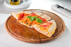 Traditional Italian closed pizza Calzone on the wooden board on the served restaurant table. Selective focus. Stock Images
