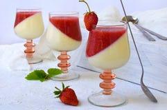 Traditional italian dessert panna cotta in glass with berry jello. Layered vanilla milk strawberry dessert on light background. Stock Photography