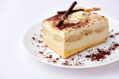 Traditional italian dessert tiramisu/ tiramisu cake with cream mascarpone and cacao powder on a white plate. White background. Clo. Se up. Isolated royalty free stock photos