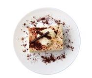Traditional italian dessert tiramisu/ tiramisu cake with cream mascarpone and cacao powder on a white plate. White background. Clo. Se up. Isolated royalty free stock image