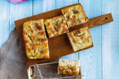 Traditional Italian focaccia with rosemary, tomato on a cutting board stock photography