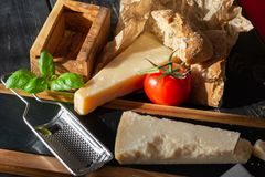 Traditional italian food - aged Italian parmesan hard cheese Par. Migiano-Reggiano with cheese knife, tomato, basil, olive oil stock image