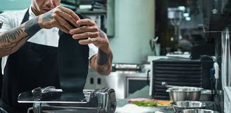 Traditional italian food. Cropped image of chef`s hands with tattoos rolling a black dough through pasta machine. In the kitchen. Close up royalty free stock photography